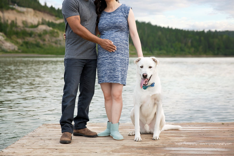 A mixed race couple pose on a dock along the North Saskatchewan River in Edmonton for maternity photos.