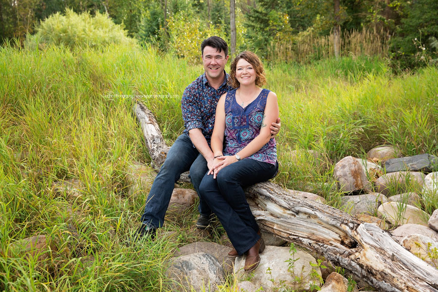 A man and wife sit together on a fallen log at Larch Sanctuary