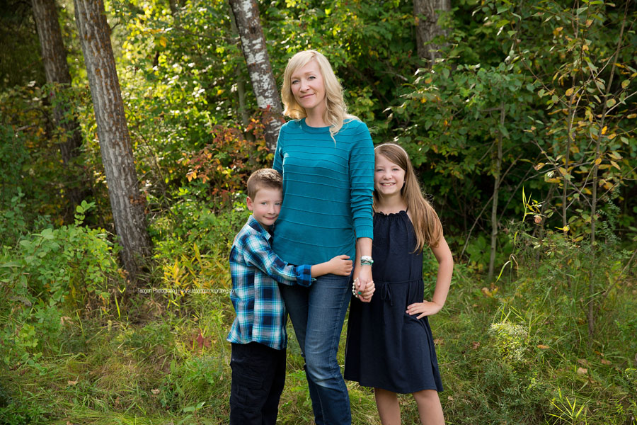 A mother hugs her two school age children during an Edmonton family photography session