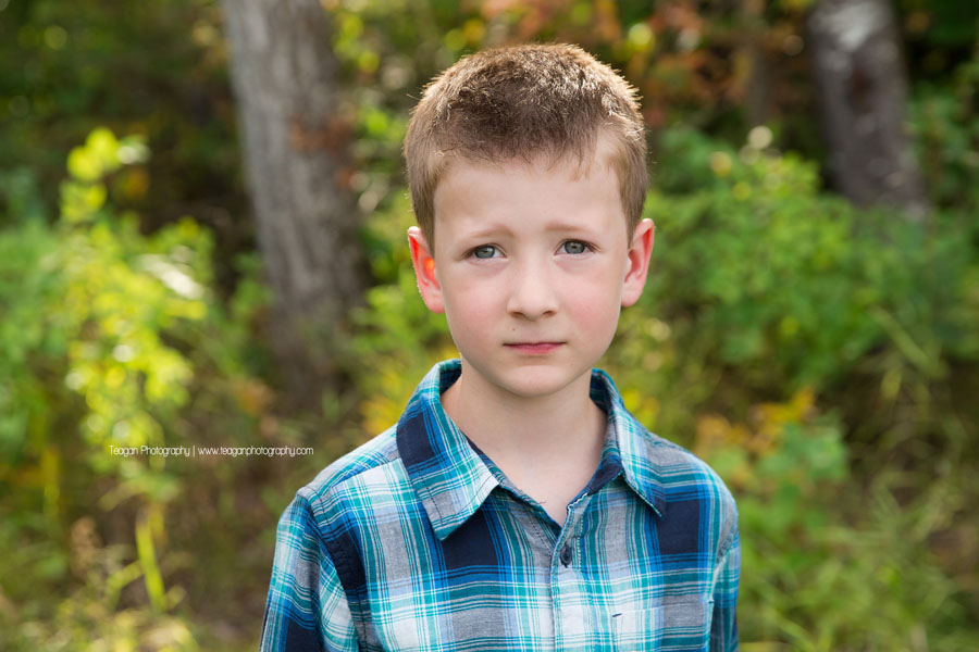 A school aged boy wearing a blue and black checkered button up shirt poses for a portrait in Edmonton