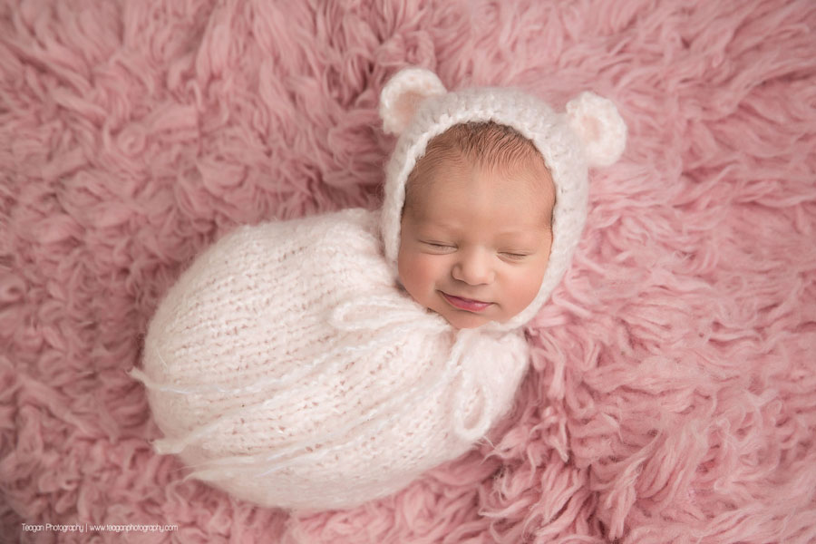 An Edmonton newborn baby sleeps on a pink rug in a pink scarf while wearing a knit pink bear hat