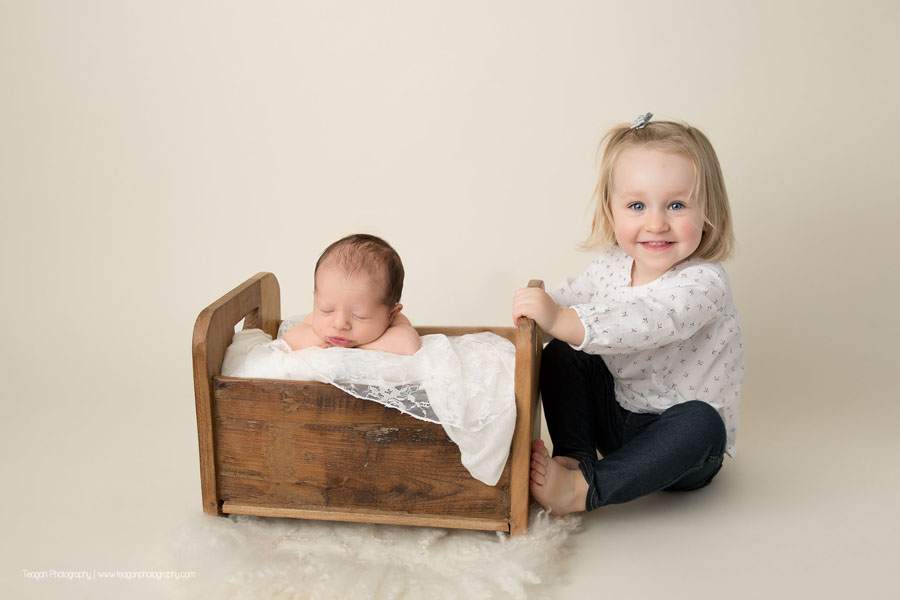 A big sister poses on the floor with her newborn baby who is sleeping in a wooden bed