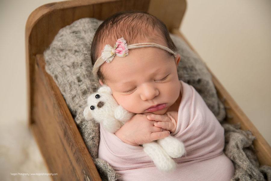 A baby girl is wrapped in pale pink and asleep in a wooden bed