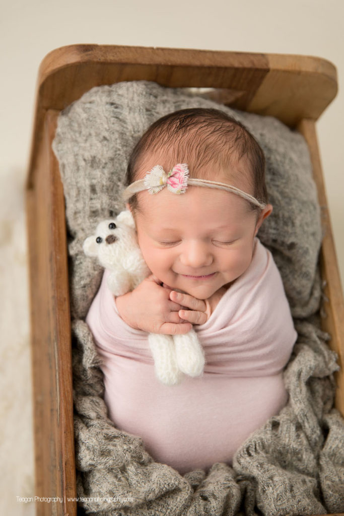 A baby girl is wrapped in pale pink and asleep in a wooden bed while hugging a small white teddy bear