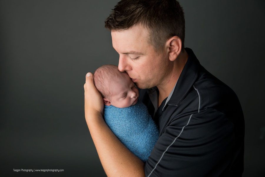 A new father kisses the head of his baby boy