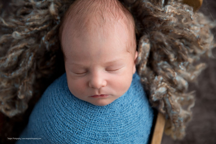 Wrapped in a blue scarf is a newborn baby boy asleep in a wooden bed