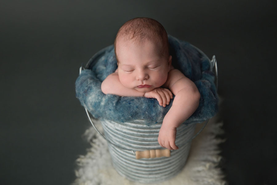 An Edmonton newborn baby sleeps in a metal bucket stuffed with denim blue wool fluff