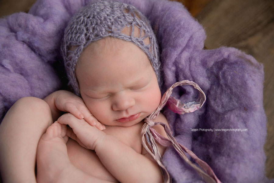 A newborn girl sleeps in purple fluff during an Edmonton newborn photography session