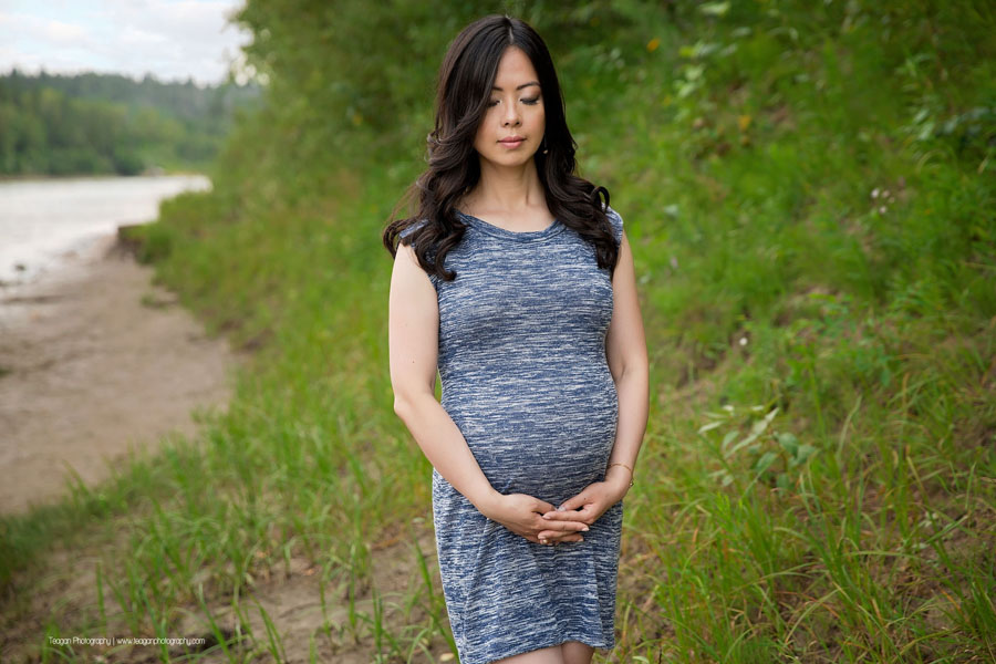 A pregnant Chinese woman hugs her belly during maternity photos in Edmonton