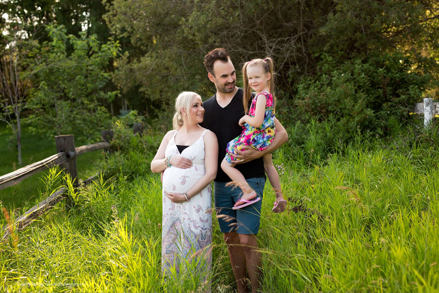 Mom and dad snuggle their toddler daughter in tall grasses during an maternity session