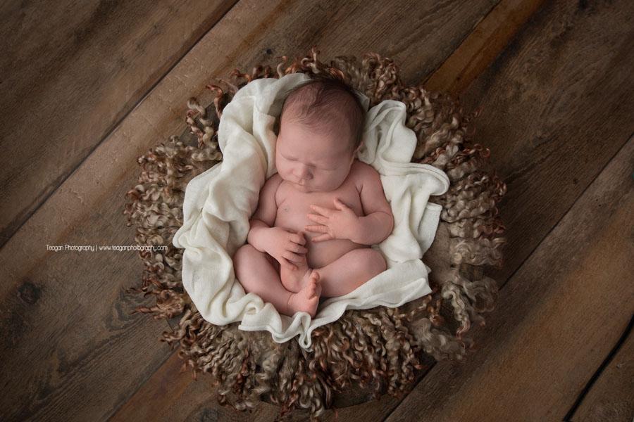 A newborn boy sleeps tucked in a cream colour blanket on a hardwood floor