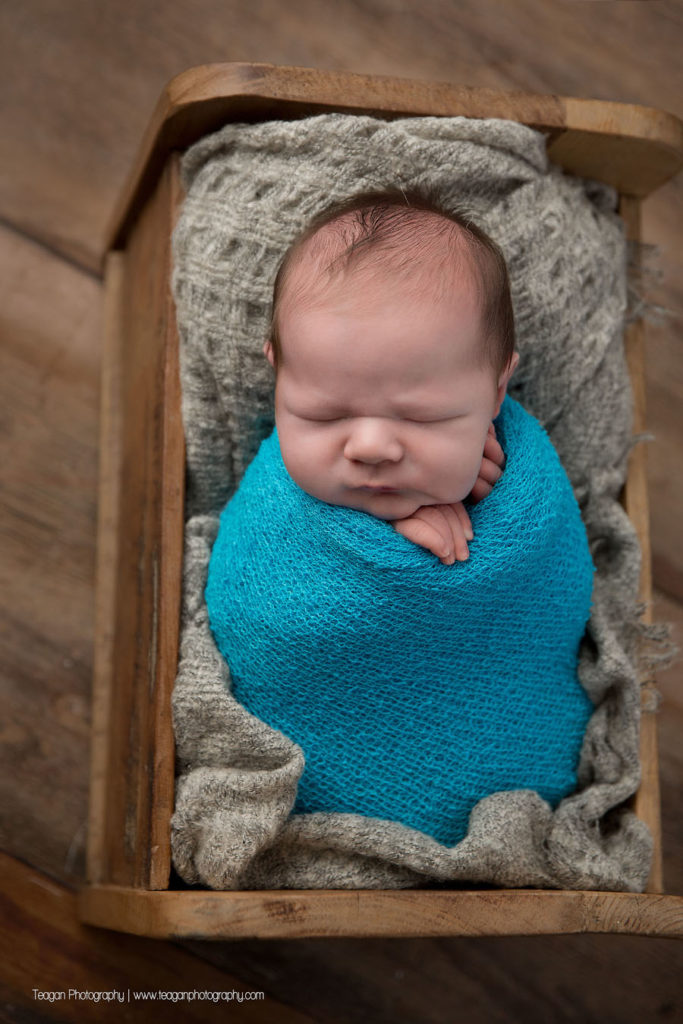 Wrapped in a turquiose blanket is a sleeping newborn baby boy