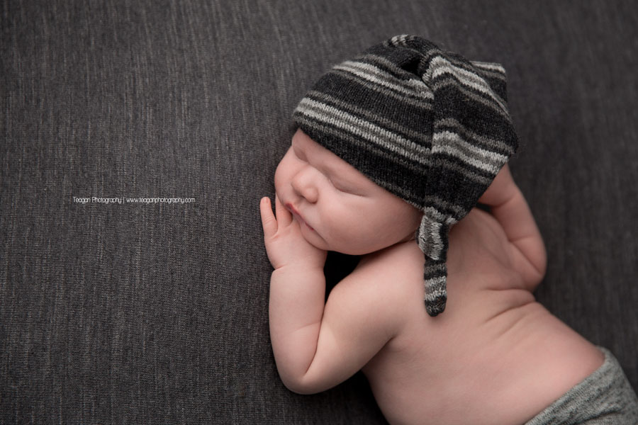 An infant boy sleeps on a grey blanket with a black and grey striped hat