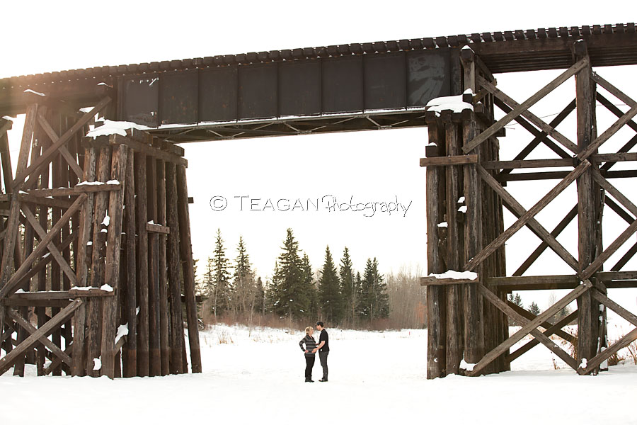 A couple expecting their first child pose together on the frozen Sturgeon river in St Albert