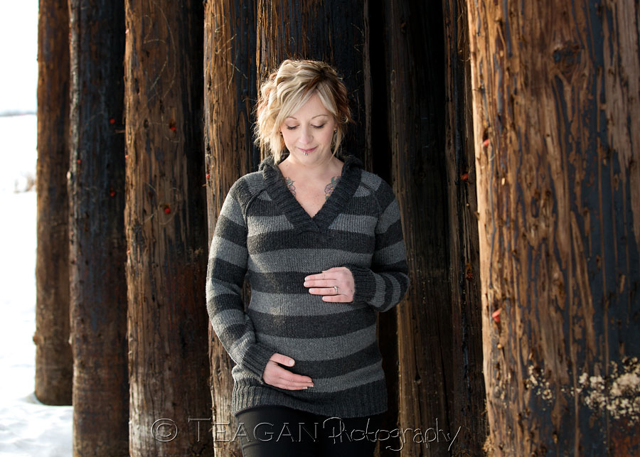 A pregnant woman hugs her tummy in front of the St Albert Trestle Bridge