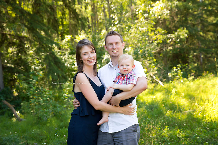 A family pose with their son in the grass at Larch Sanctuary in Edmonton
