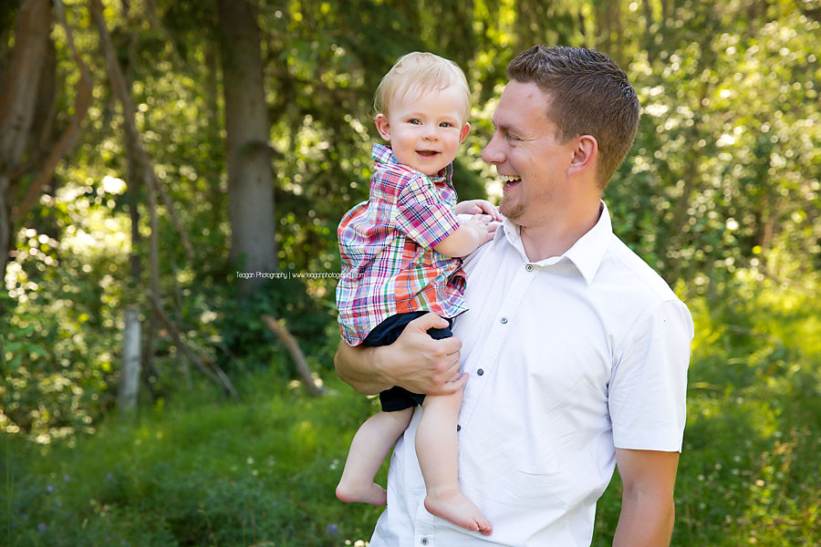 A dad laughs with his one year old son during a family photo shoot in Edmonton