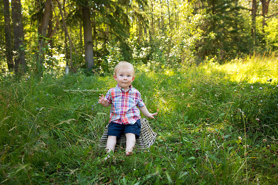 A ones year old boy sits on a basket in the grass at Larch Sanctuary in Edmonton