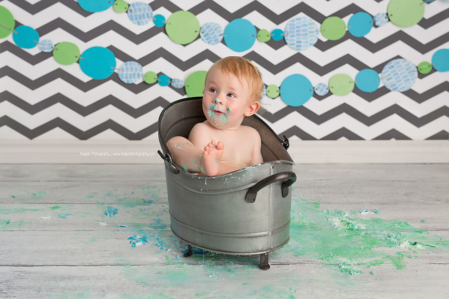 bathing in a small metal bathtub is a one year old birthday boy after his Edmonton cake smash