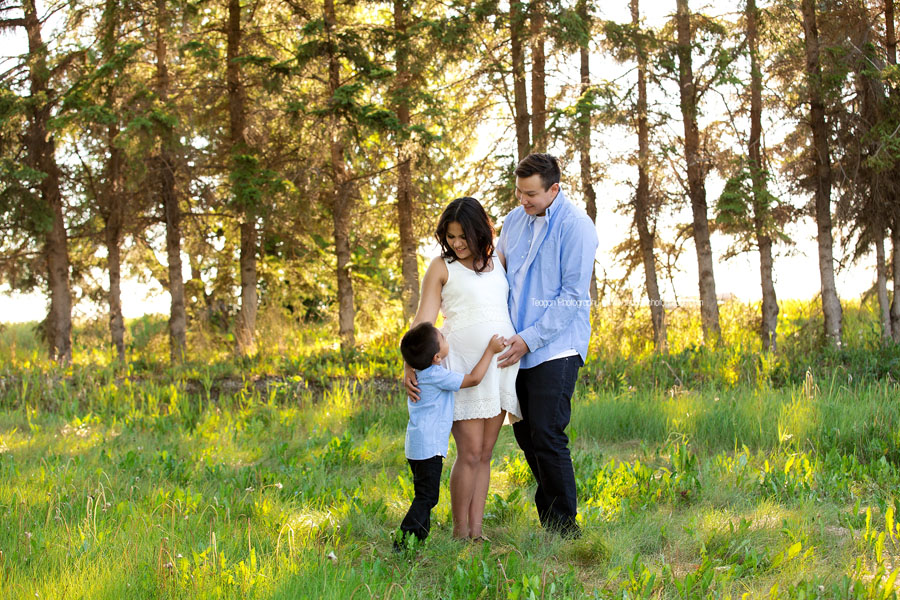 The summer sun filters through the trees during  an Edmonton maternity photoshoot