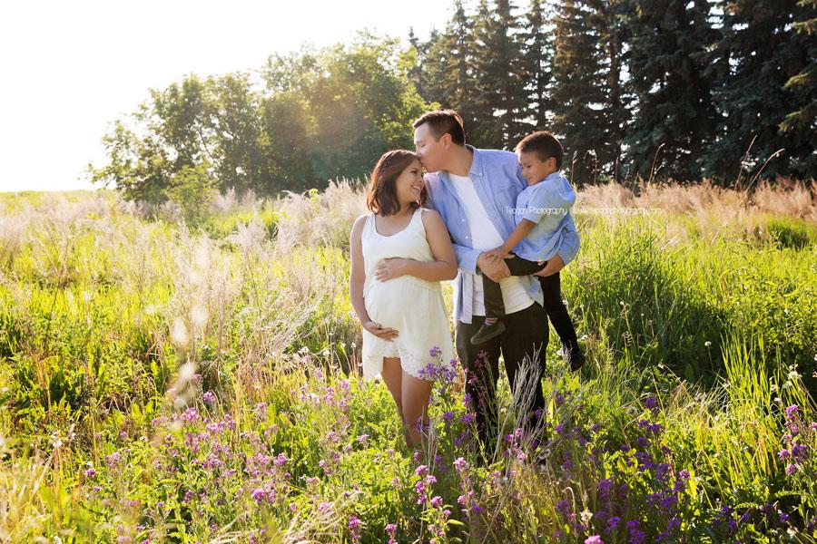 Apregnant woman is kissed by her boyfriend in a field of purple flowers