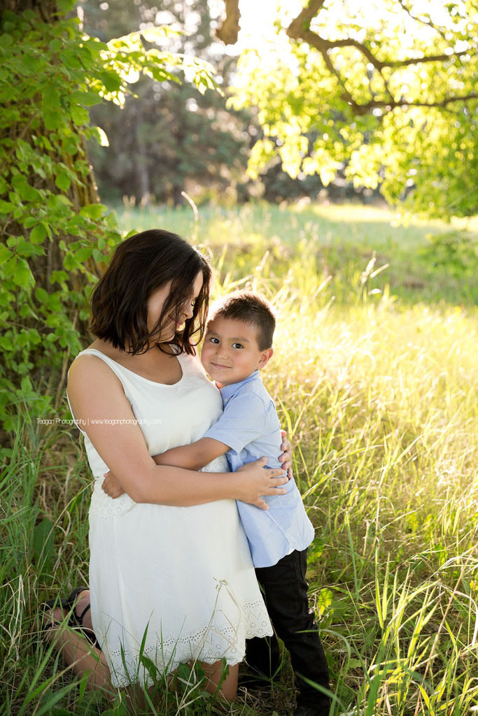 A beautiful pregnant woman hugs her belly while posing for maternity photos in an Edmonton field