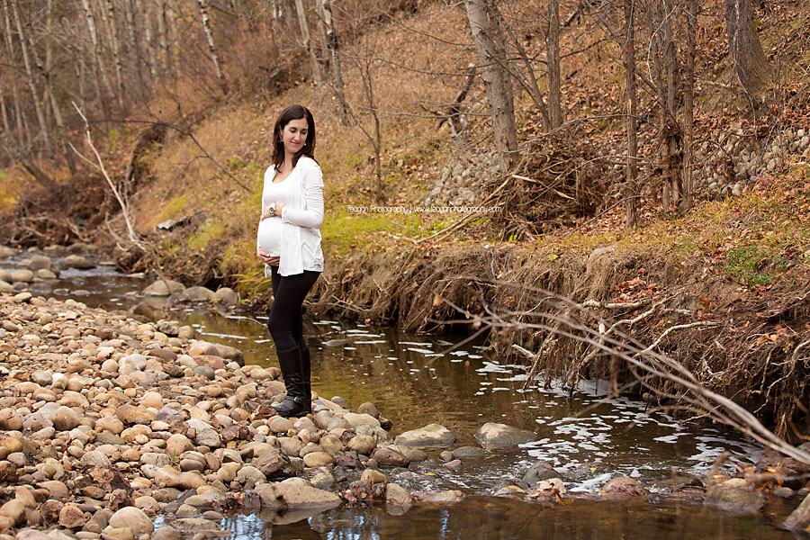 A Spanish woman with dark hair and a white shirt poses in the Millcreek ravine during Fall maternity photos in Edmonton