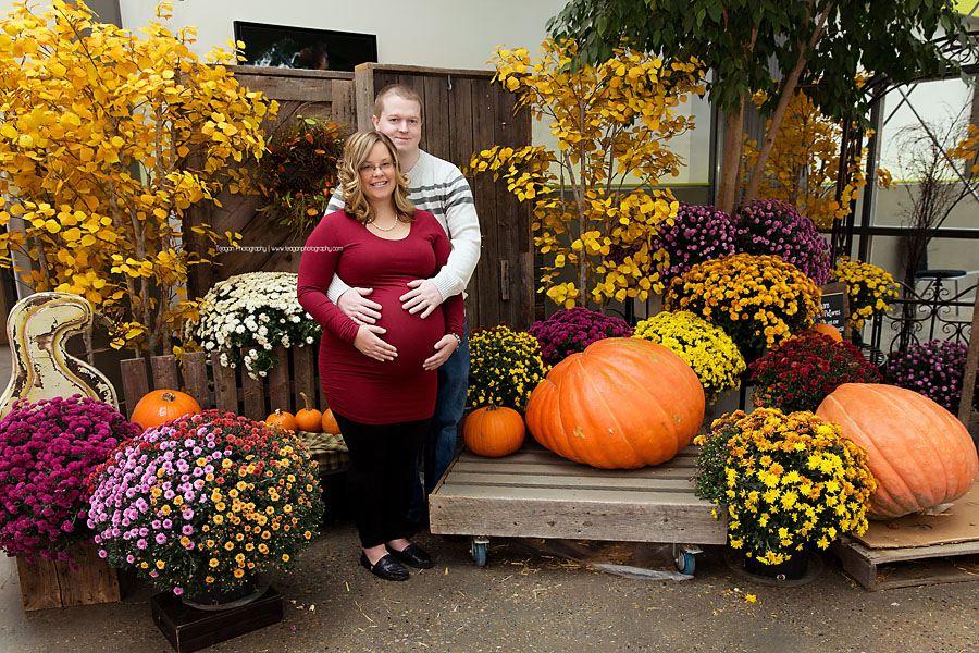 Posed in front of the fall foliage is a pregnant Edmontoncouple