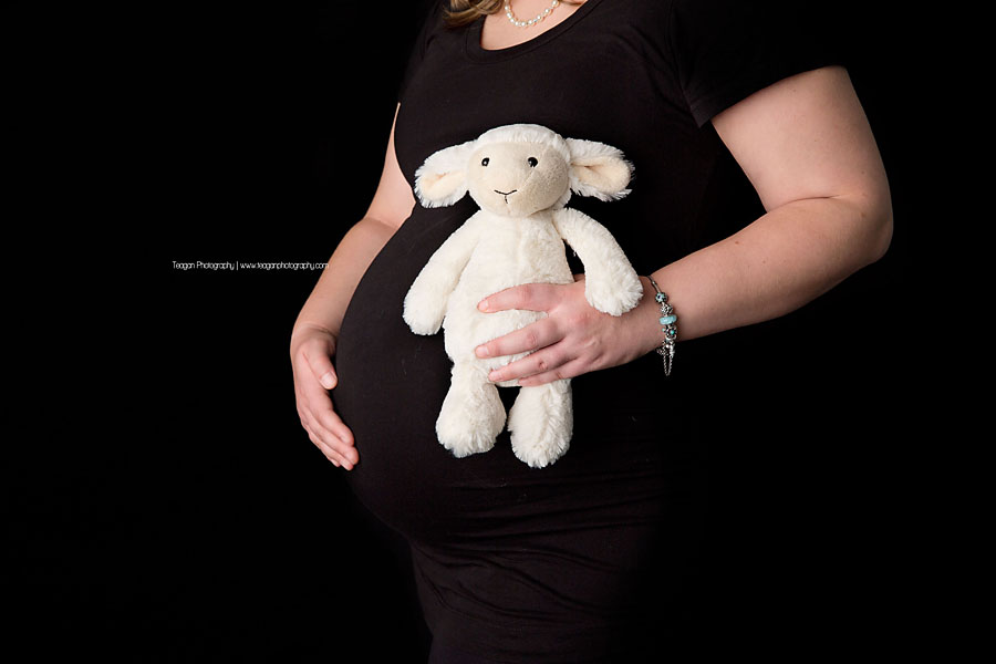 A woman holds a white toy lamb to up to her pregnant belly