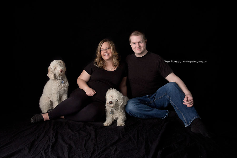 A couple sits on a black blanket with their two white dogs.