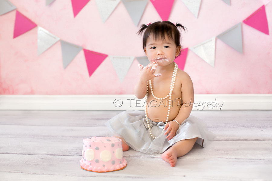 Celebrating her first birthday in Edmonton with a caks smash photo shoot is an Asian girl
