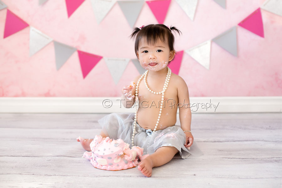 Celebrating her first birthday with a caks smash photo shoot is an Asian girl