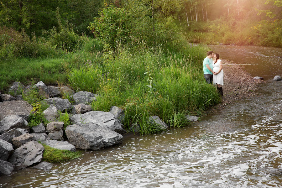 A husband and wife are expecting their first baby and celebrate with Edmonton maternity photos in the summer along the Millcreek stream