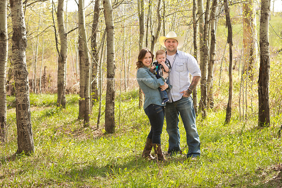 A family wearing country attire sit together during an outdoor photography session in Edmonton