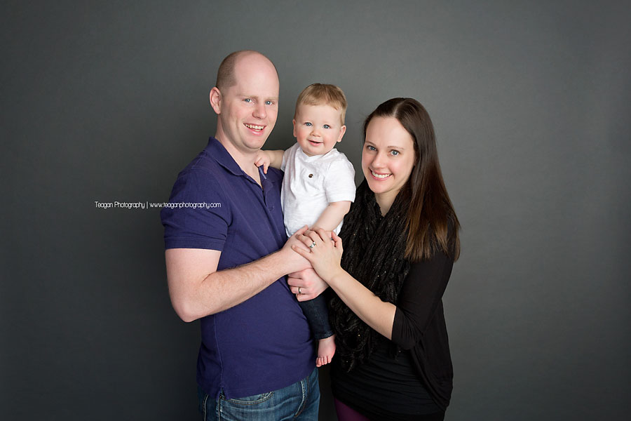 Parents hold their one year old boy during his birthday photo shoot