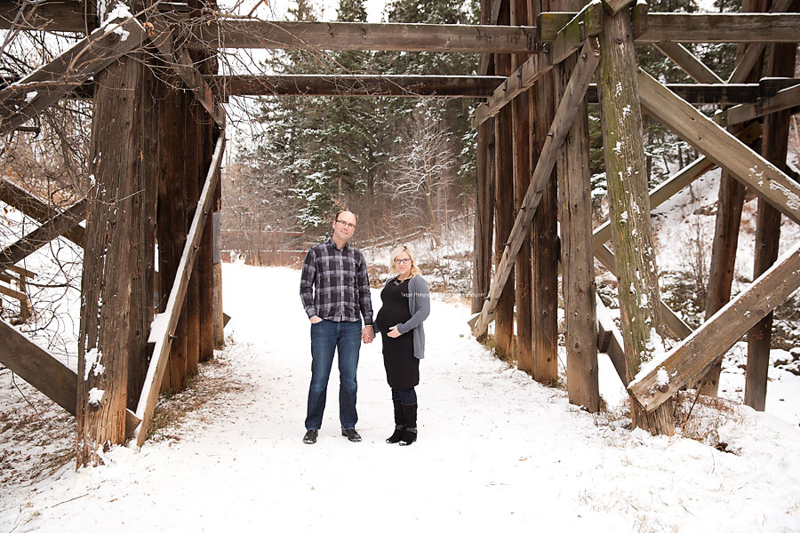 A pregnant couple stands belwo the Millcreek treselt bridge during a winter maternity photo shoot
