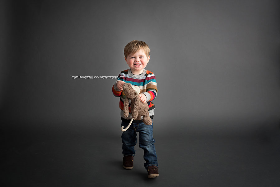 A cheeky little boy laughs as he stands on a grey backdrop