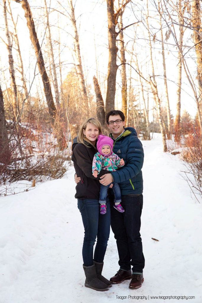 Parents snuggle with their one year old daughter in a forest in St Albert
