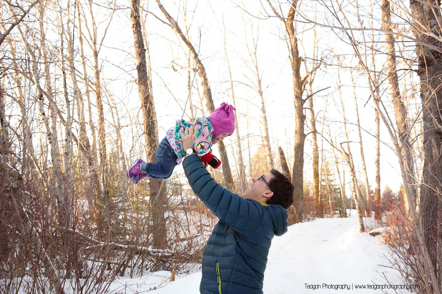 Dad plays with his snowsuit bundled daughter in St Albert