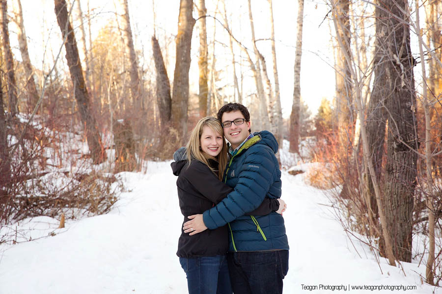 A newly engaged couple stand together during a winter photo session in St Albert