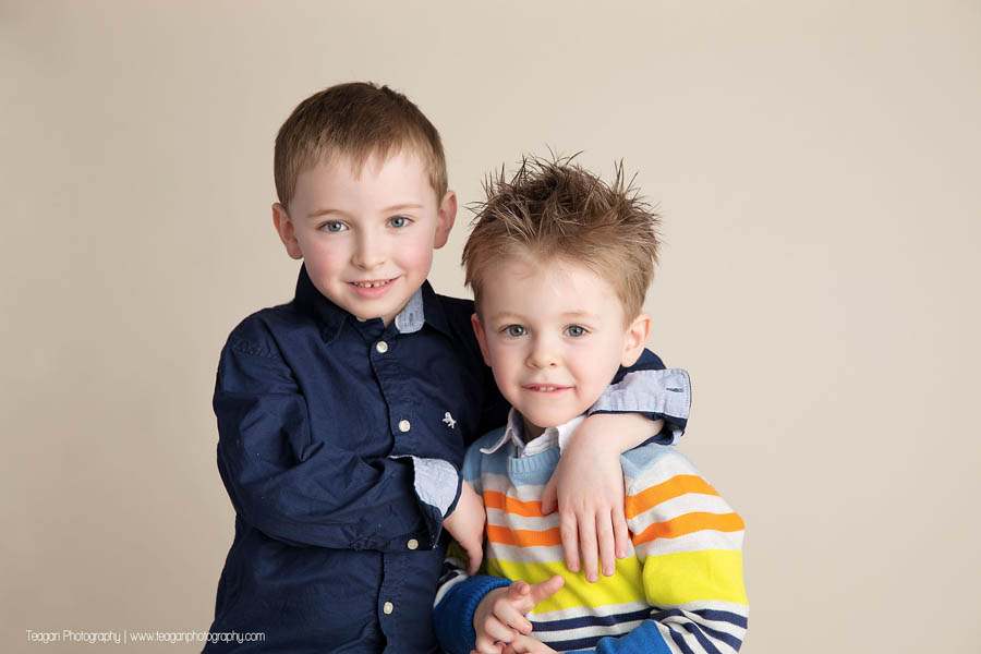 Two blonde preschool aged brothers stand together in front of a beige wall