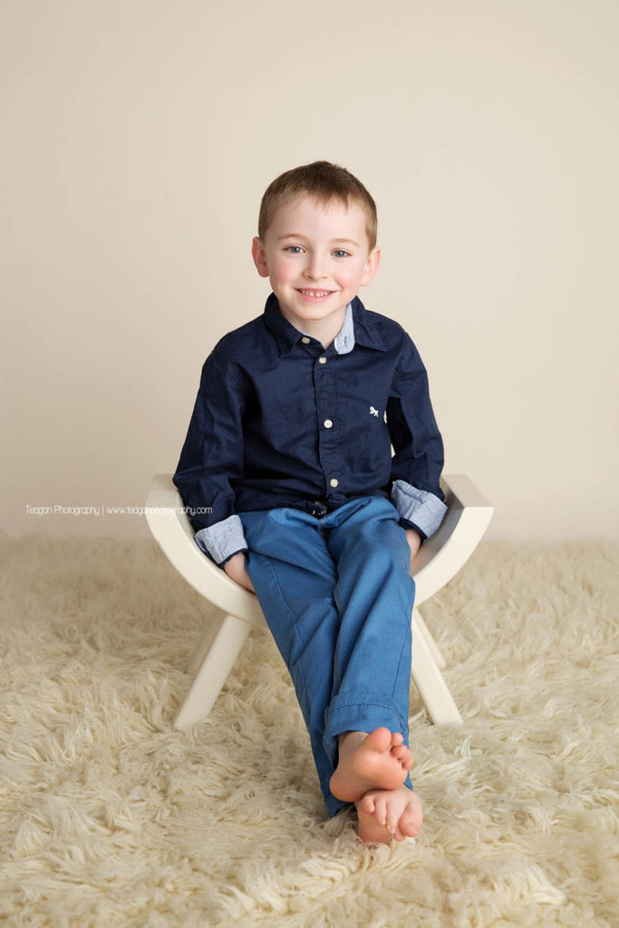 A little boy with blye eyes smiles for the camera while sitting on a white curved bench
