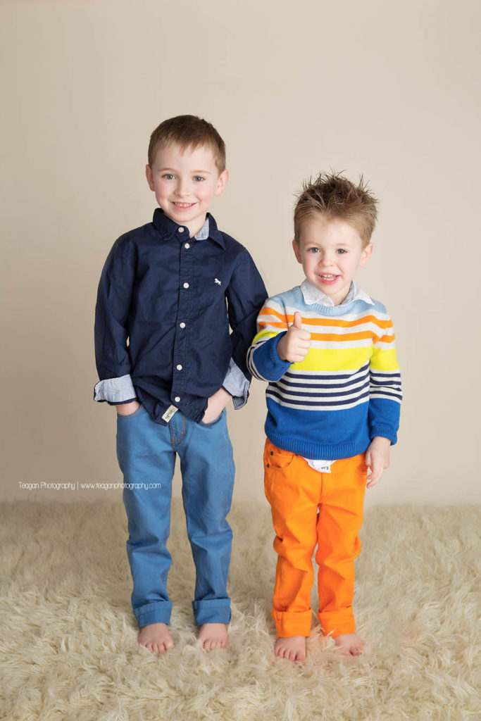 a little boy in orange pants and a striped sweater gives a thumbs up to the camera