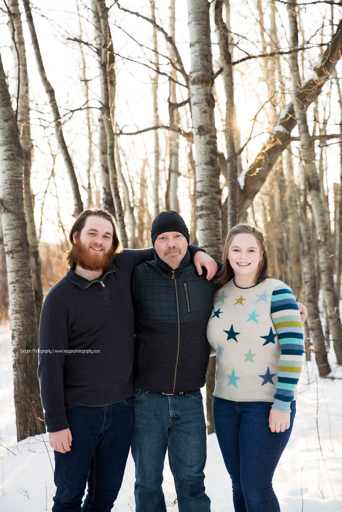 A father hugs hius two adult children in a west Edmonton forest in the winter
