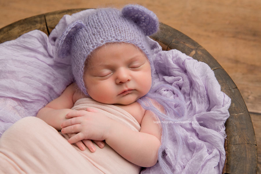 wearing a lavender bear bonnet is a newborn baby girl sleeping on a pale pink blanket