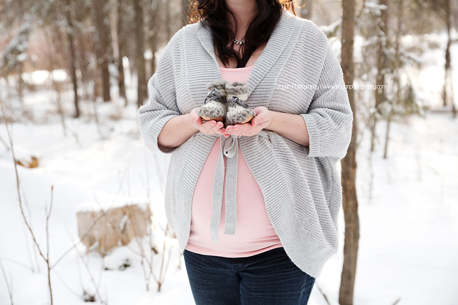 A close up of tiny knit booties and a mother's pregnant belly