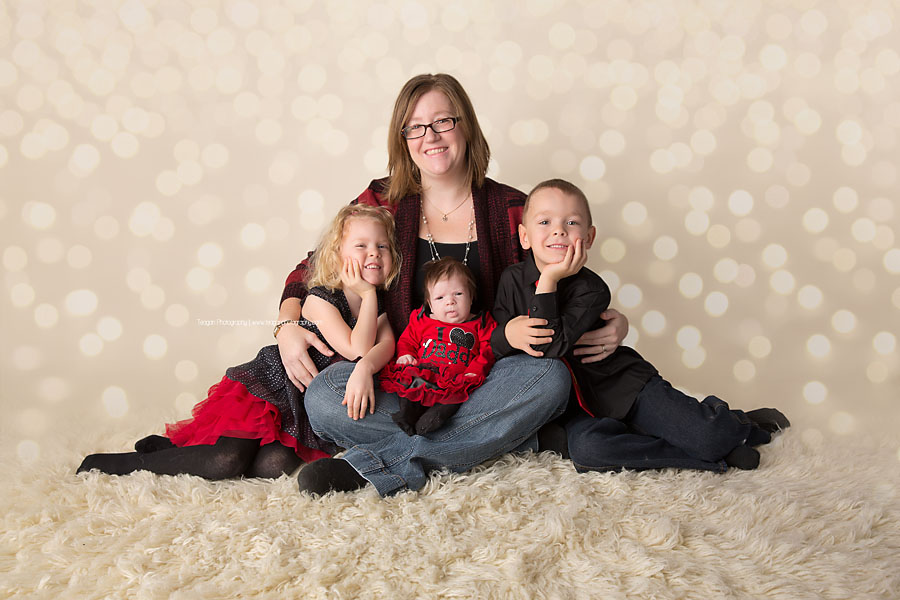 And Edmonton mom sits on a cream rug with his twin children and new baby girl