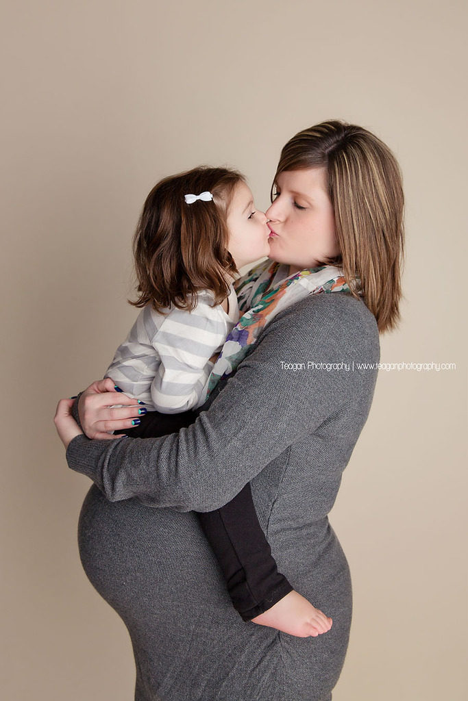 A toddler girl kisses her pregnant mother's tummy
