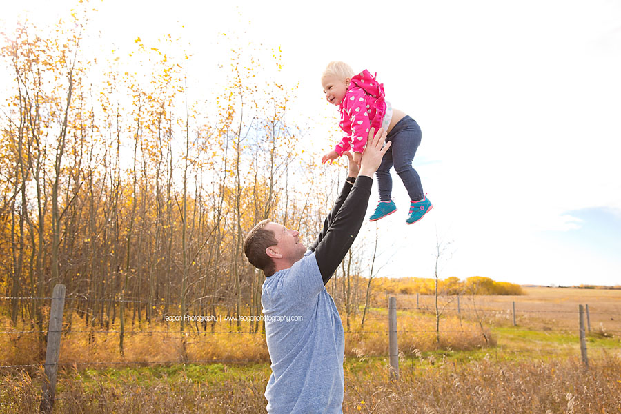 A father plays with his daughter in an Edmonton field