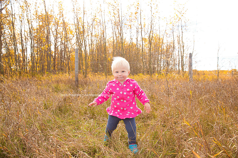 A little girl with short blonde hair runs through the dry grass in an Edmonton field
